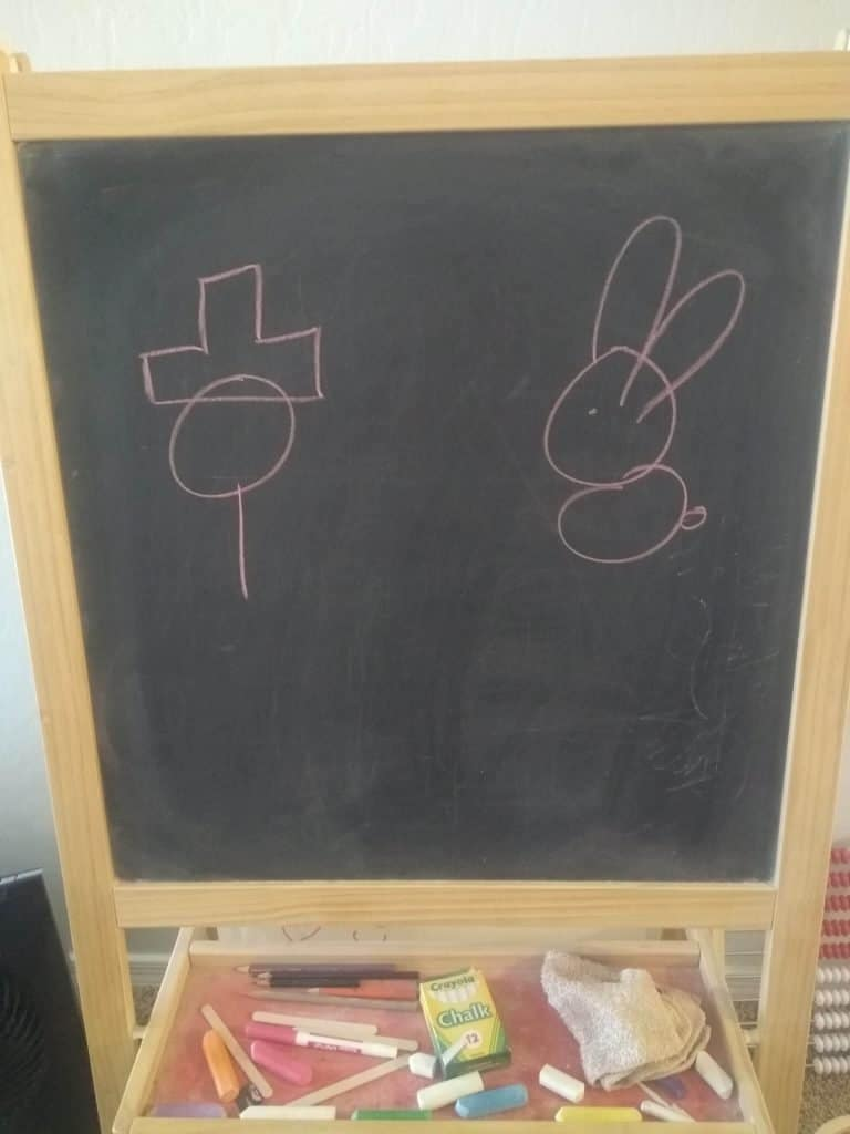 black chalkboard with pine frame. A circle with a line straight down and a hat on top (left) and right side a simple stick figure rabbit. Drawing in pink chalk.